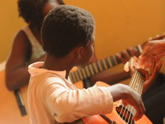 child learning guitar